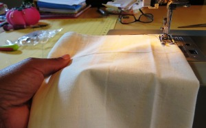 The left hand gently moves the fabric forward as it is fed through the machine.